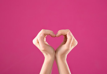 Woman making heart with her hands on color background, closeup