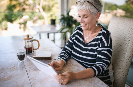 Portrait of a mature woman smiling, using her tablet at home , outside on the balcony. Beautiful elderly woman and scrolling