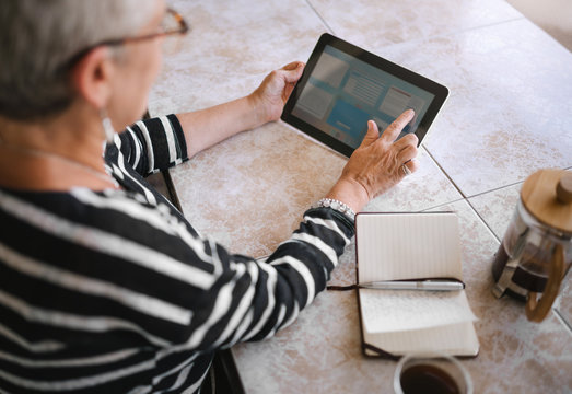 Top view of mature woman making notes interacting on a digital tablet