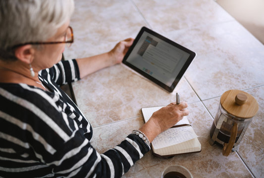 Top view of mature woman making notes in her notebook or journal while reading off the screen of a digital tablet