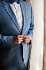 the man zips up his jacket, groom in a jacket, white tie, bridegroom's fees, business style.
