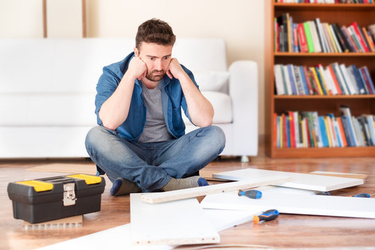 Sad young man reading the instructions to assemble furniture