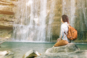 Female backpacker resting in front of waterfall.