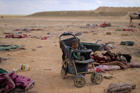 Child sits in a baby carriage near the village of Baghouz