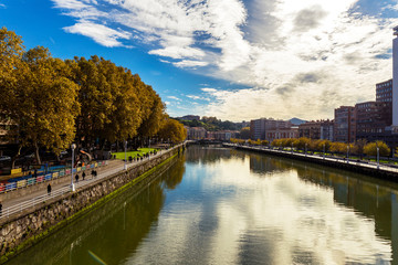 view of Nervion river in Bilbao city with people wlaking . Spain