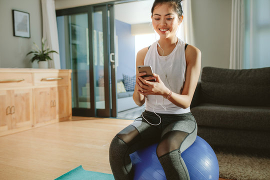 woman with smartphone relaxing on a fitness ball