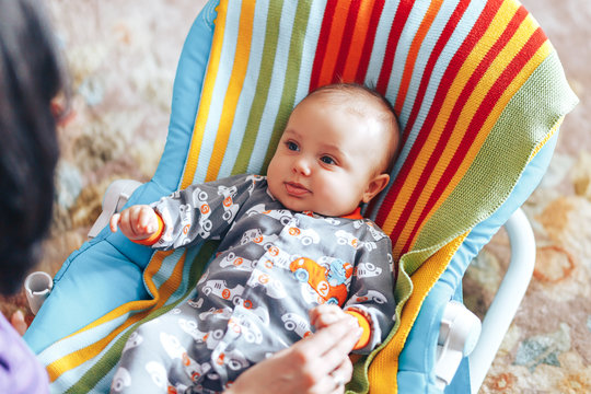 nice blue eyed Baby child relaxing on a sunbed or a deck chair colored bouncer at home