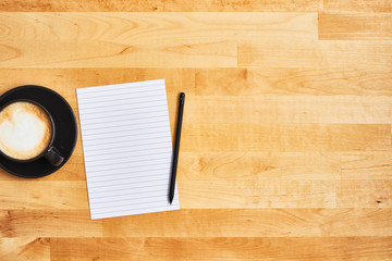 Cup of coffee or cappuccino with an empty sheet of paper and pencil on yellow wooden table. Top view. Copy space for text.