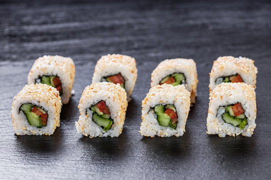 Vegeterian makizushi roll with cucumber and tomato arranged on slate plate background
