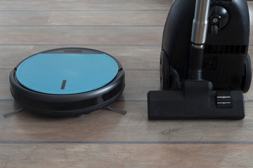 Robot vacuum and regular vacuum cleaner next to each other