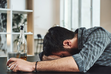 Drunkenness is temporary suicide. Alcohol abuse: drunk man lying down on a table with glass of whiskey still in hand