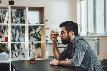 Alcohol is the anesthesia by which we endure the operation of life. Drunk man with glass and bottle of whiskey sitting at table in kitchen. Drinking alone. Male alcoholism concept