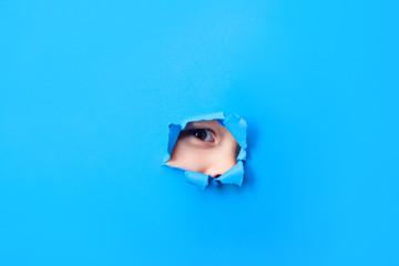 Spy concept. Kid's eye peeking through hole in paper. Spying through hole in blue paper. Spy eye looks through paper wall. Boy's eye is watching us through hole. Eye peering in sheet of paper hole.