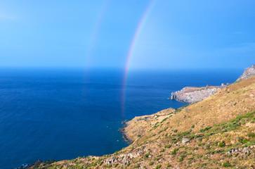 Wild hilly coastline of Creta island with a rainbow