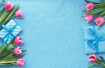 Blue background with wrapped gift boxes and eucalyptus twigs around empty center