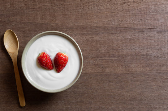 top view of natural yogurt with strawberry in a ceramic bowl on wooden table, copy space. healthy food concept.