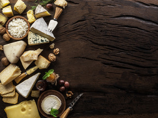 Assortment of different cheese types on wooden background. Top view.