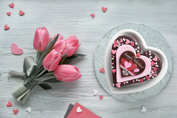 """Valentine heart cake with chocolate, sugar decorations and text """"Happy Valeitine"""" and pink tulips"""