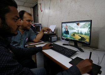 A designers works on a graphic image of Indian Air Force pilot Abhinandan Varthaman, who was captured and later released by Pakistan, to be printed on saris inside a sari manufacturing factory in Surat