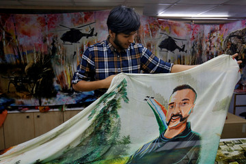 A salesman displays a sari with a printed image of Indian Air Force pilot Abhinandan Varthaman, who was captured and later released by Pakistan, inside a sari manufacturing factory in Surat