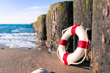 Nostalgic Life Buoy Beach Sea Shore Scene / Vintage red and white miniature life buoy at row of groynes on sandy shore of baltic sea (copy space)