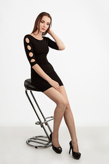 Portrait of a beautiful happy girl with different emotions in a black dress and shoes in the studio on an isolated background