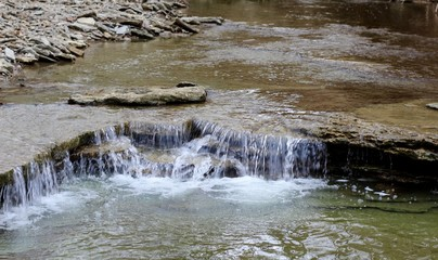 The water flowing over the rocks in the stream.