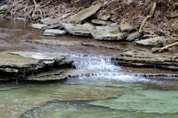 A small waterfall in the flowing water of the creek.