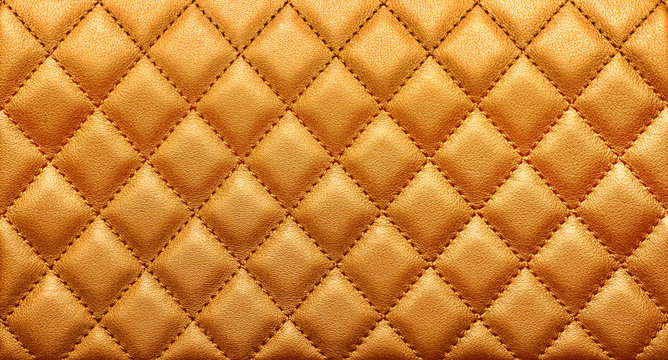 Close-up texture of genuine leather with rhombic stitching. Rich gold color