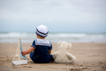 Baby boy sitting on the beach near the water and plays with a toy ship and bear toy