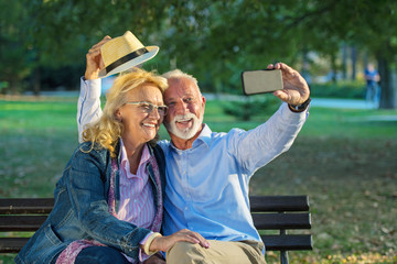 Senior couple taking a selfie photo with smart phone in a park
