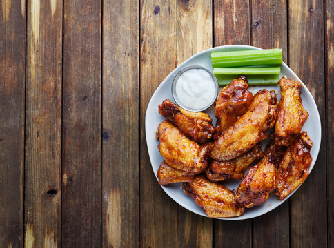 buffalo chicken wings with ranch and celery in overhead composition including copyspace on wooden rustic table top