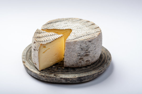 Round mature French Tomme cheese with cutted piece close up isolated