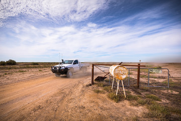 A farmer drives out of a large farm property in outback New South Wales.