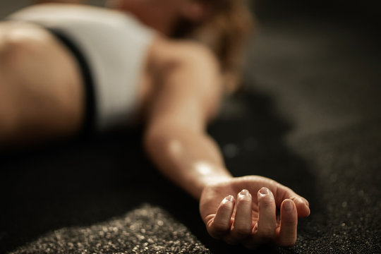 Close up of exhausted athlete resting on the floor after sports training.
