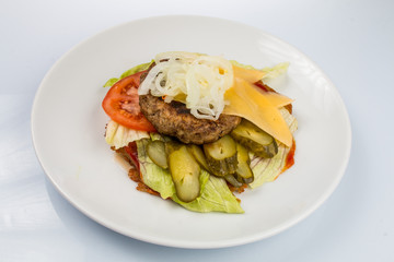 cheeseburger with beef cutlet, bacon, tomatoes and cheese slices, seasoned with sauce and green salad for a restaurant menu on a white isolated background