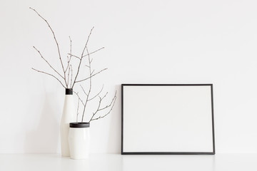 white frame mock up and dry twigs in vase on book shelf or desk. White colors..