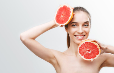 Image of excited cute young woman isolated over white wall background holding grapefruit
