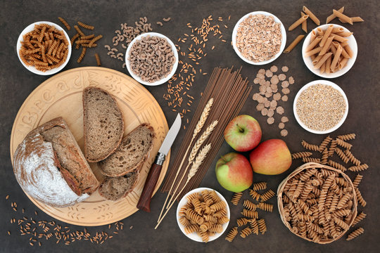Food for a high fibre diet with apples, whole grain rye bread, whole wheat pasta, oatmeal, oats, bran flakes and wheat sheath. High in vitamins, smart carbs, antioxidants and minerals.