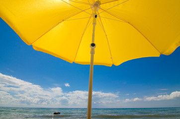 Sun umbrella on a sandy seashore on a hot July day. People are swimming in the sea.