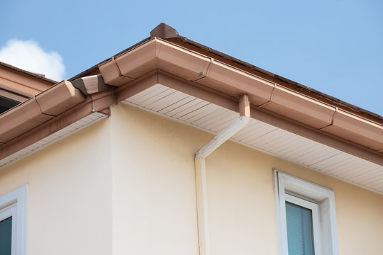 brown steel rain gutter  with blue sky. concept : repair roof in summer before rainy season.