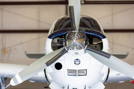 Small white and blue  plane in hangar, small cockpit, private, straight on