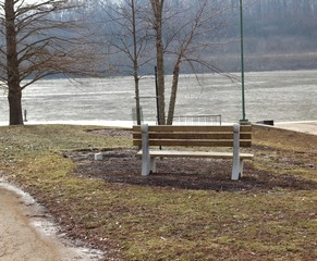 A empty wood park bench overlooking the lake.