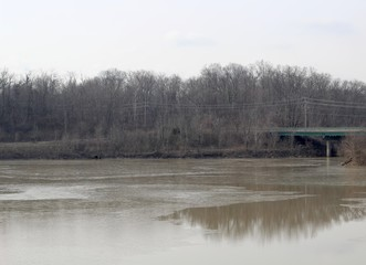 A view of the partly frozen lake in the park on a cloudy day.