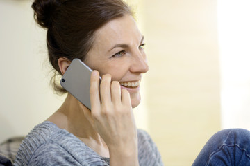 Woman on the phone at home with smartphone is happy