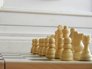 White pieces aligned on a chessboard ready to start the game