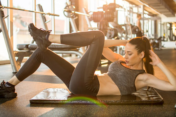Fitness girl doing bicycle crunch exercise on exercise mat in gym