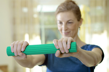 Woman with pain in arm or tendonitis is exercising muscles with a flexible torsion bar