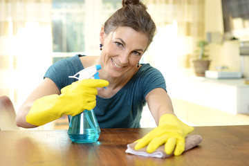 Woman with cleaning spray and wipe wipes wooden table