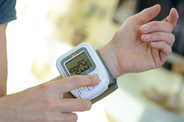 Patient with sphygmomanometer measures blood pressure at home